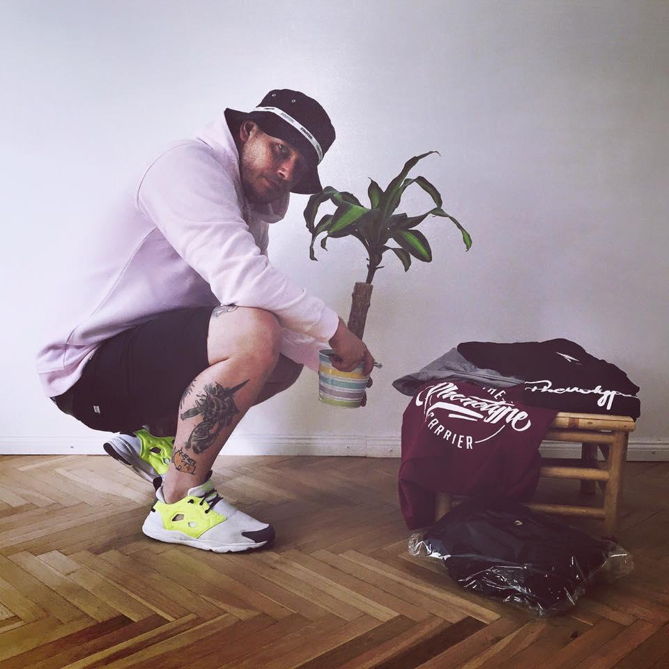 Na zdjęciu znajduje się kucający mężczyzna ubrany w kapelusz. Trzyma w dłoniach roślinę doniczkową