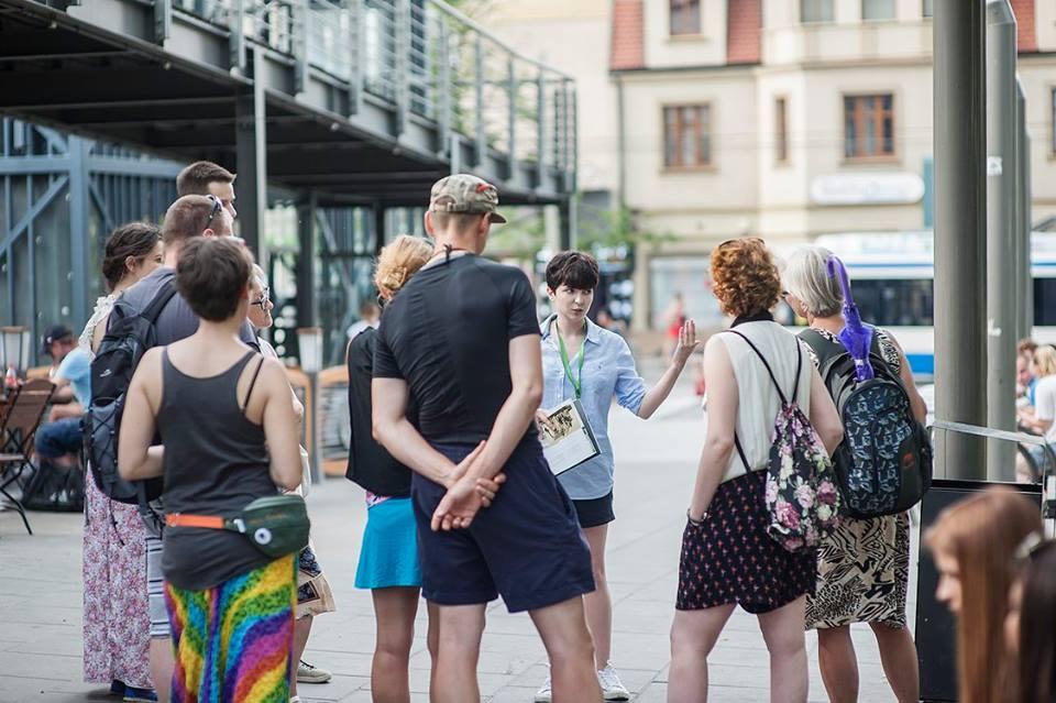 Kilka osób stojących w przestrzeni publcznej, na ulicy