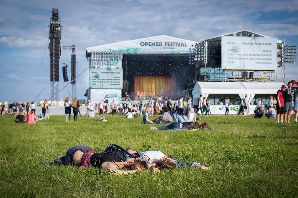 Teren fesitwalu Opener, zielona trawa na której leżą ludzie i scena