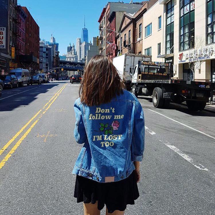 Dziewczyna stojąca tyłem na ulicy, ubrana w jeansową kurtkę