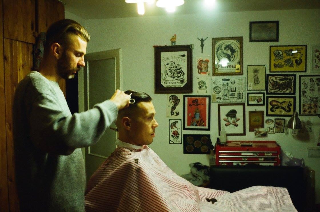 Zdjęcie przedstawia dwóch mężczyzn. Jeden siedzi w fotelu fryzjerskim, drugi wykonuje strzyżenie.