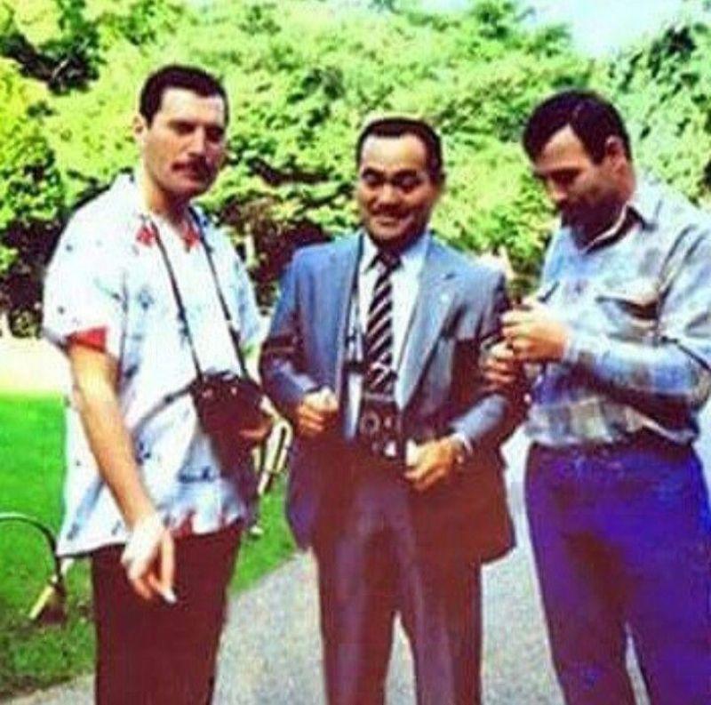 na zdjęciu widzimy trzech mężczyzn, jeden ma aparat na szyi, drugi garnitur a trzeci patrzy się w dół