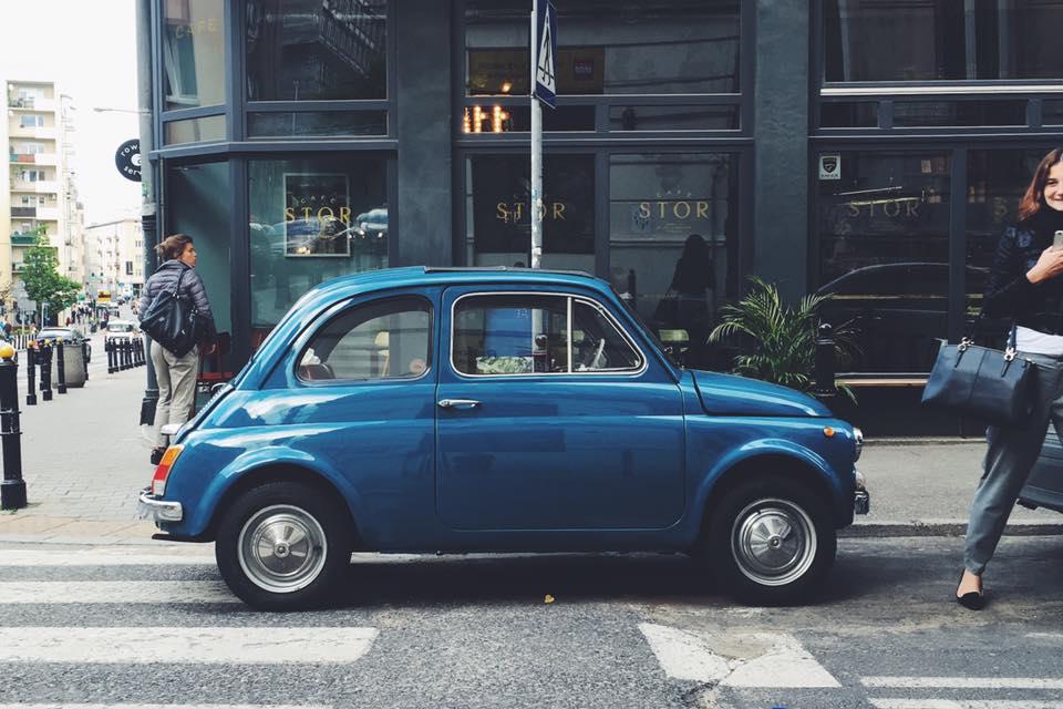zdjęcie przedstawia kawiarnię z zewnątrz, przed nią stoi mały, oldschoolowy samochod
