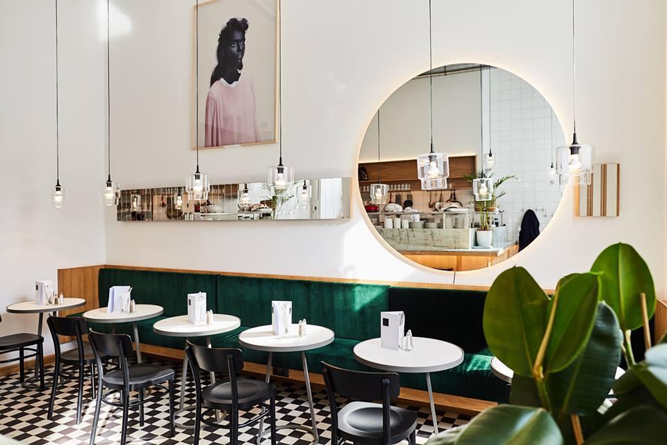 zdjęcie przedstawia wystrój w środku kawiarni, duże lustro na ścianie oraz krzesła, stoliki i podłużne siedzenia obite welurem zielonym
