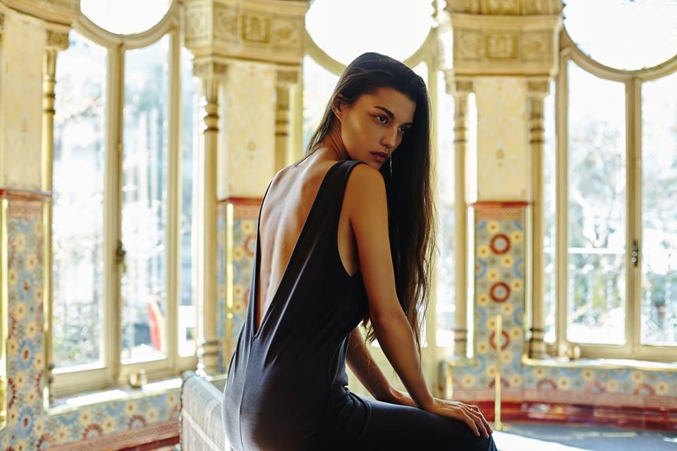 Kobieta siedząca na stoliku ubrana w czarną sukienkę z dużym wycięciem na plecach