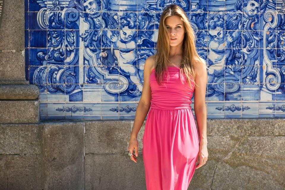na zdjęciu widzimy modelkę ubraną w długą zwiewną różową sukienkę. stoi na tle muralu wzorzystego