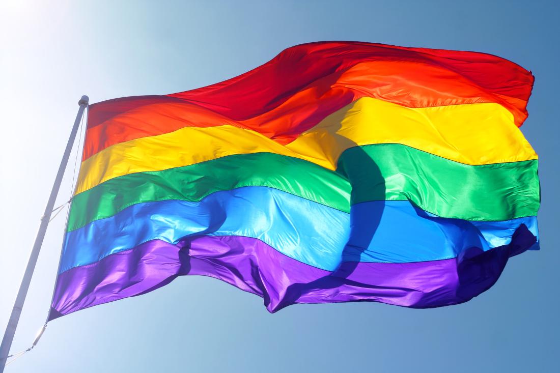 na zdjęciu jest falująca na wietrze tęczowa flaga