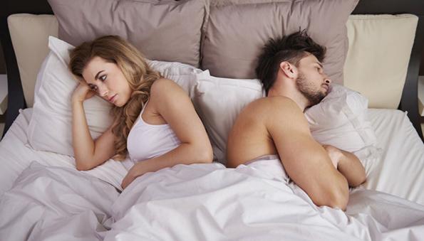 Kobieta i mężczyzna leżacy w łóżku odwróceni do siebie plecami