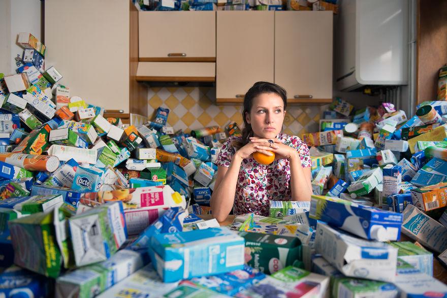 zdjęcie przedstawia kobietę siedzącą w kuchni a wokół niej jest pełno pustych opakowań po mleku zajmujących całą kuchnię
