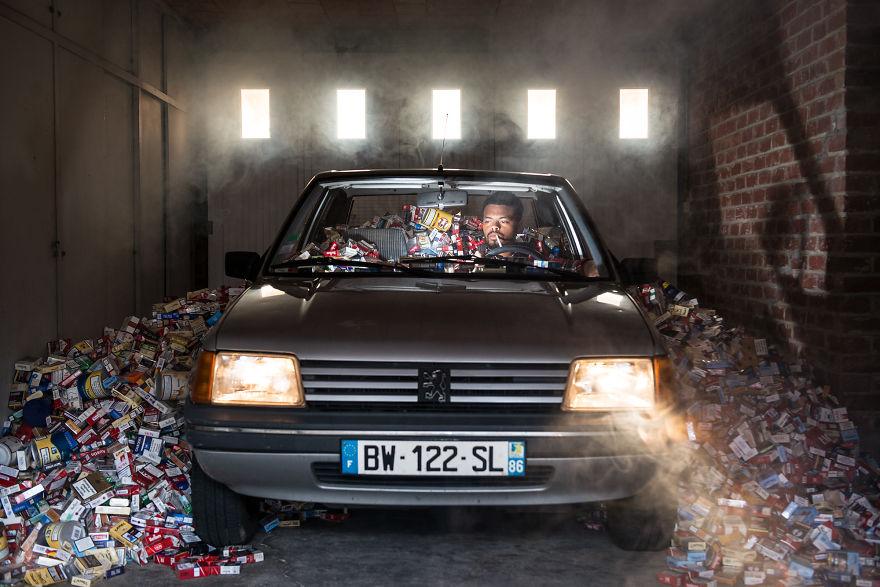 zdjęcie przedstawia mężczyznę siedzącego w samochodzie w garażu, a wokół samochodu jest pełno pustych opakowań po papierosach