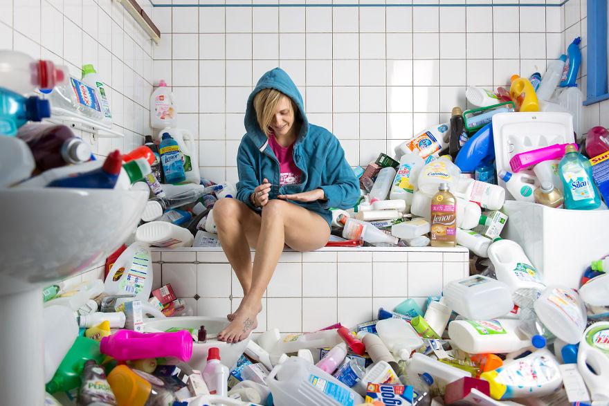 zdjęcie przedstawia dziewczynę siedzącą na wannie, a wokół niej jest cała łazienka zagracona pustymi opakowaniami po proszkach do prania, płynach do płukania itp