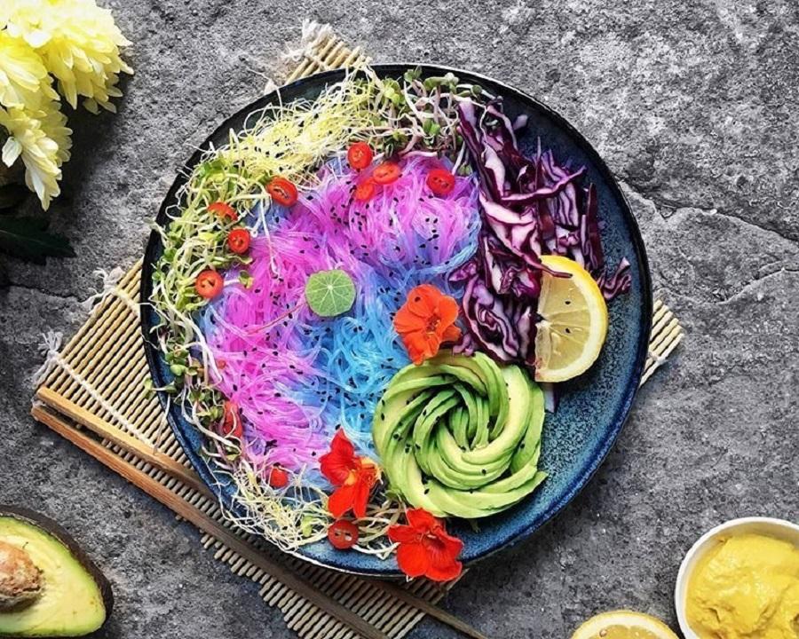 Zdjęcie przedstawia miskę kolorowego makaronu w dodatkiem pokrojonego jak róża awokado, plastrów kapusty czerwonej oraz jadalnych, czerwonych kwiatów.