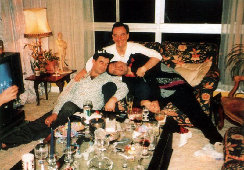 na zdjęciu widzimy trzech mężczyzn siedzących na kanapie, a przed nimi stoi stół pełen kieliszków