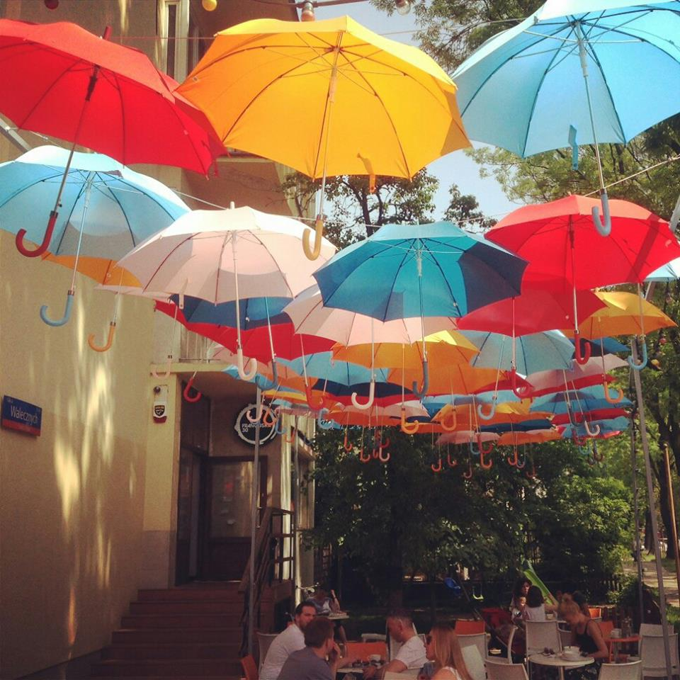 Zdjęcie przedstawia kawiarnię z zewnątrz, ogródek oraz kolorowe parasole wiszące nad stolikami