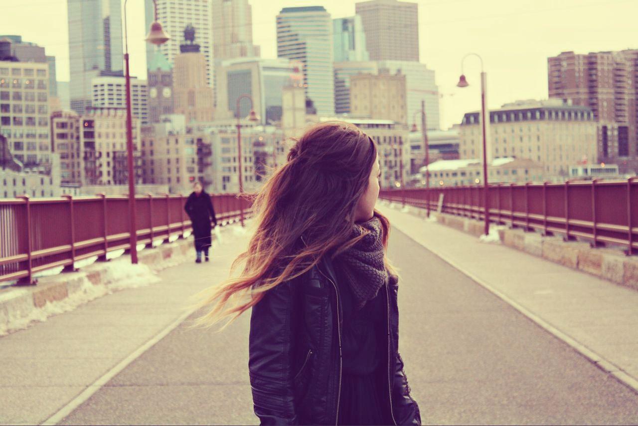 Dziewczyna stojąca na moście z odwróconą do tyłu głową