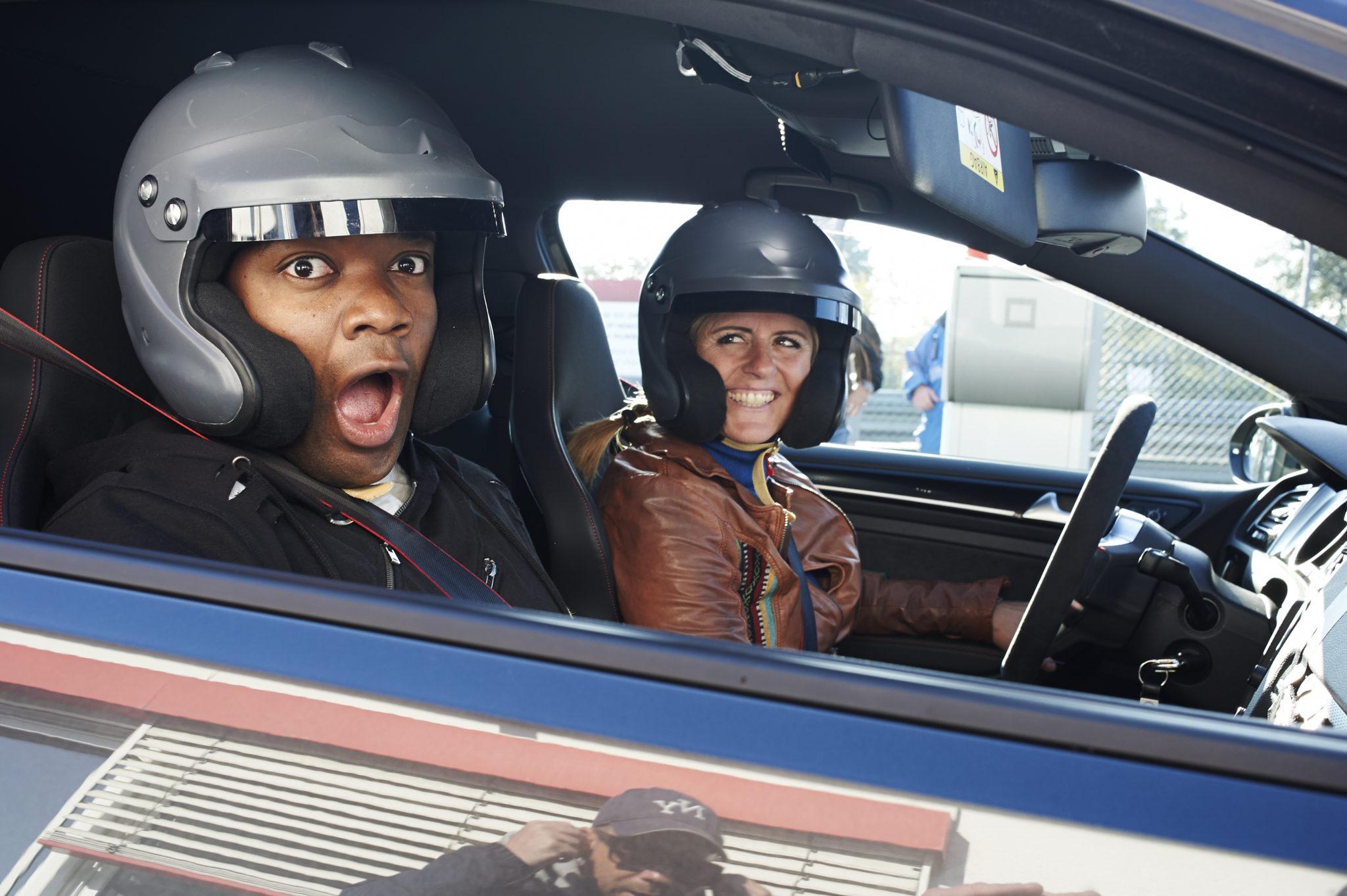 Czarnoskóry mężczyzna w kasku na fotelu pasażera, a obok kobieta w kasku