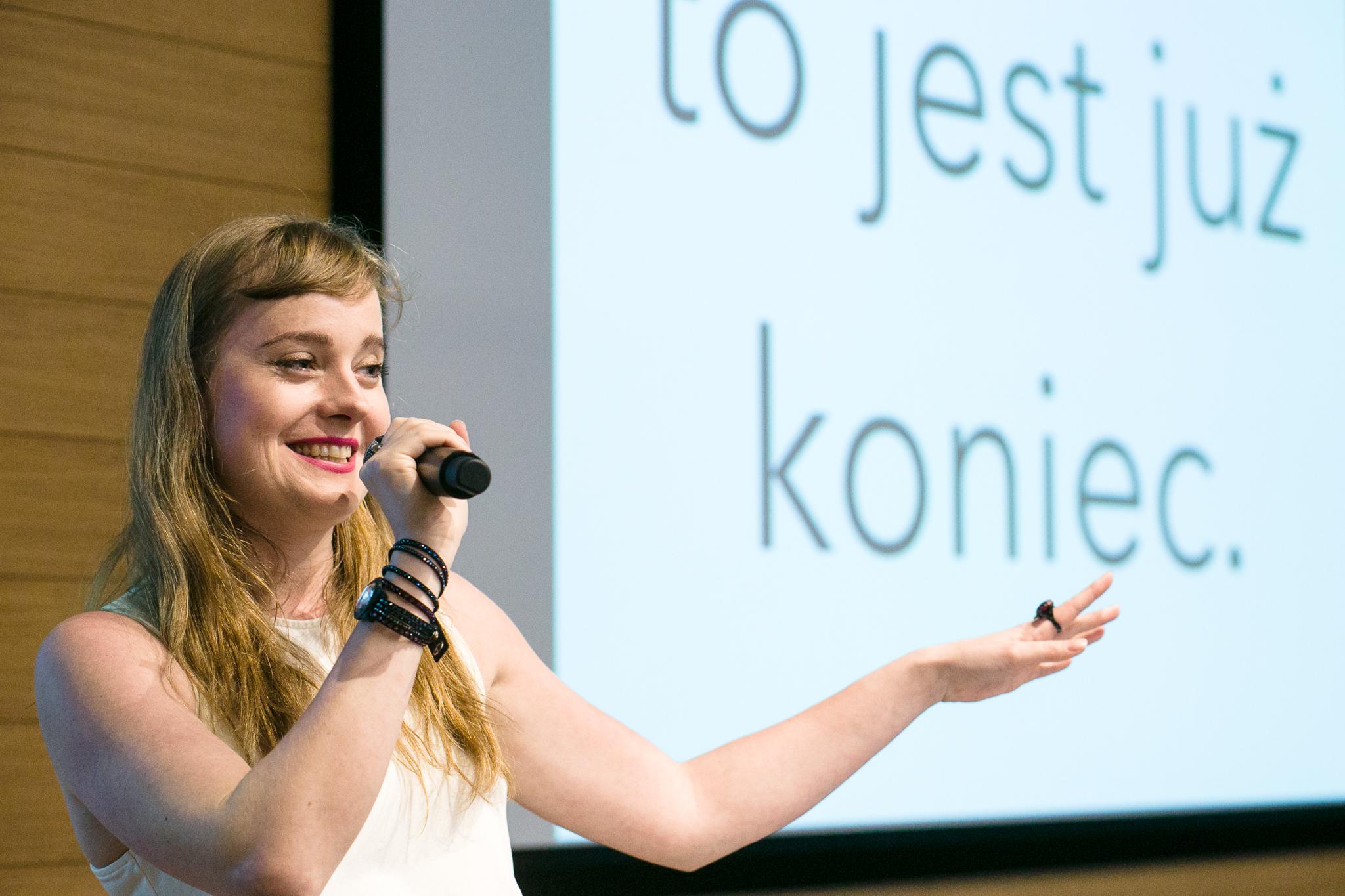 Dziewczyna w białej bluzce z mikrofonem w dłoni