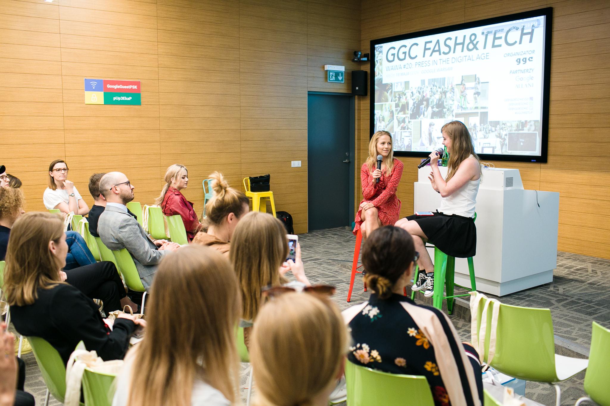 Dziewczyna w czerwonej sukience i dziewczyna w biało-czarnej sukience, w tle ludzie siedzący na krzesłach.