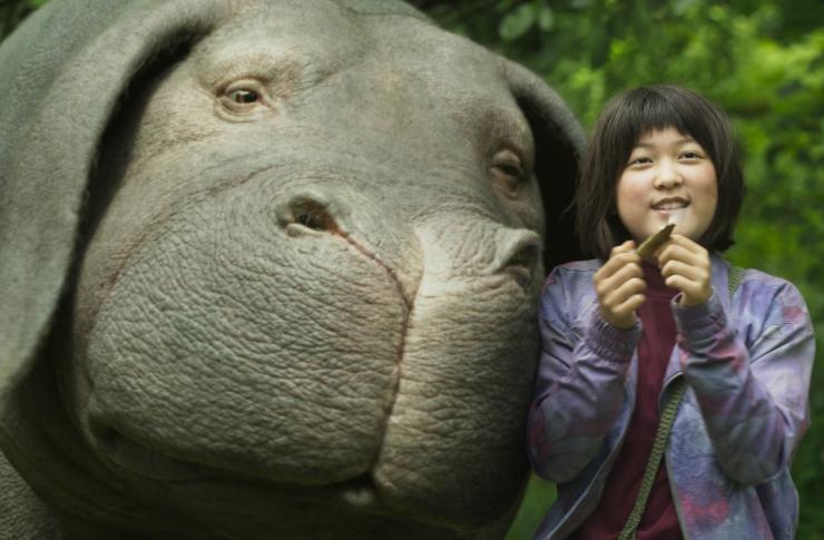 Azjatycka dziewczynka, a obok niej duża, zmutowana świnia