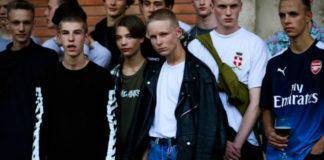 Kilku modeli stojacych przed budynkiem w ktorym odbyl sie pokaz mody, kazdy z nich ubrany w bardzo streetwearowym dresiarskim stylu