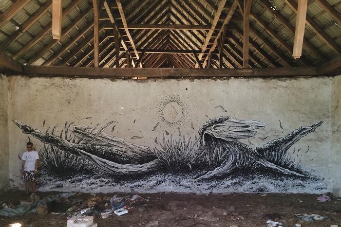 Mur pod drewnianym pomalowana czarno bialo szarymi farbami mural przedstawiajacy szkielet nieznanego stwora obok stoi mezczyzna ubrany w biala koszulke i kolorowych krotkich spodenkach przed murem widac porozrzucane smieci kartony stare szmaty a wszystko na brudnym brunatnym piachu z gdzieniegdzie rosnacymi malymi kepkami zniszczonej trawy