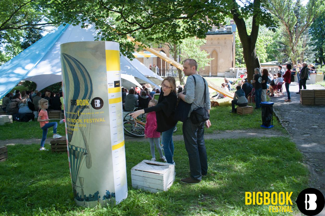 Ludzie stojący przed tablicą informacyjną