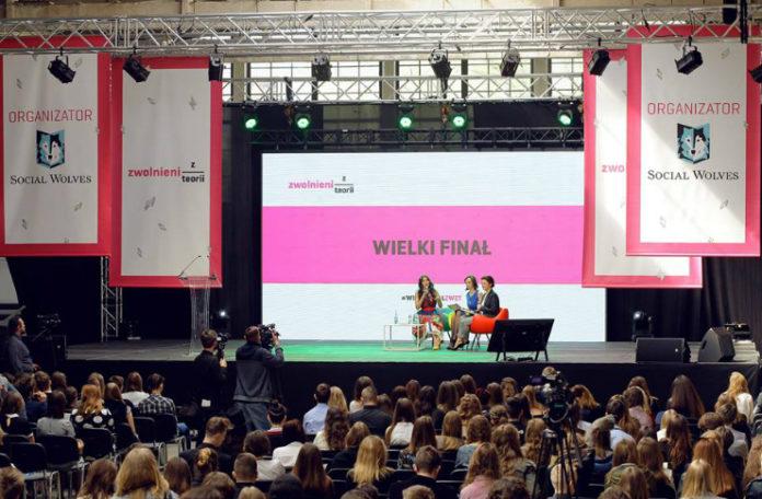 Sala wypełniona ludźmi oraz scena z biało-różową grafiką