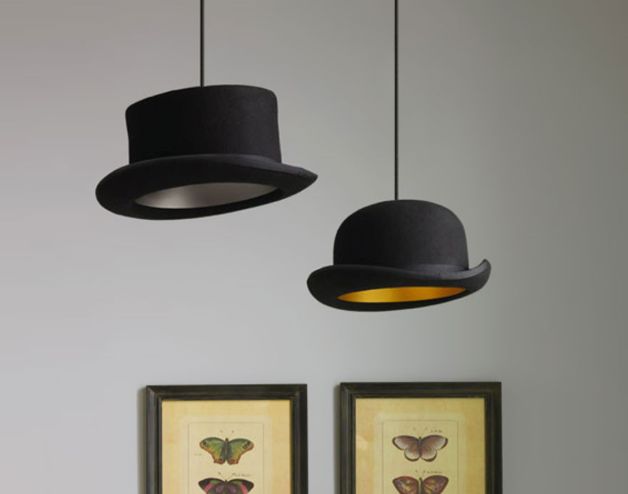 Zdjecie kapeluszy zwijajacych z sufitu, ktore służą jako abażury. Wewnatrz nich jest żarówka, która daje swiatło. W tle widać białą sciane i ucięte do połowy obrazy.