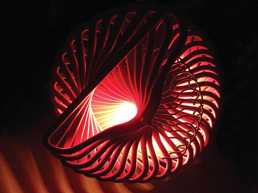 Żyrandol zmontowany z wieszaków na ubrania. Paląca się wewnatrz żarówka w połączeniu z konstrukcją daje niesamowity efekt świetlny.