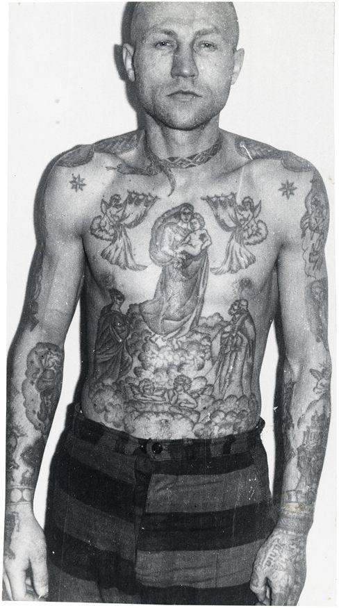 Fotografia wieźnia, który jest widoczny od pasa w górę. Na jego gołej klatce piersiowej jest dużo tatuaży. W okół szyi wytuatuowany jest wąż