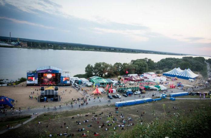 Plaża nad wodą z widocznym terenem festiwalu Audioriver