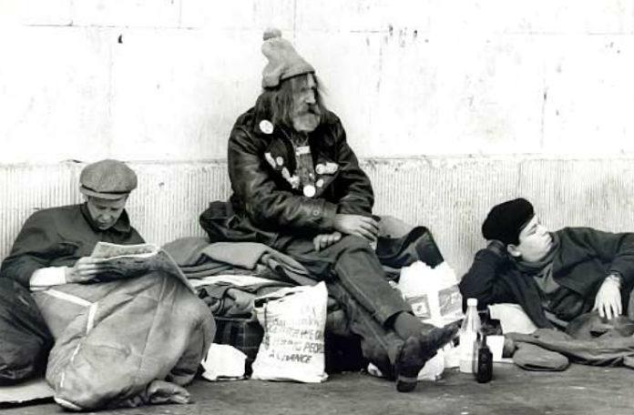 Czarno-białe zdjęcie przedstawiające troje bezdomnych mężczyzn