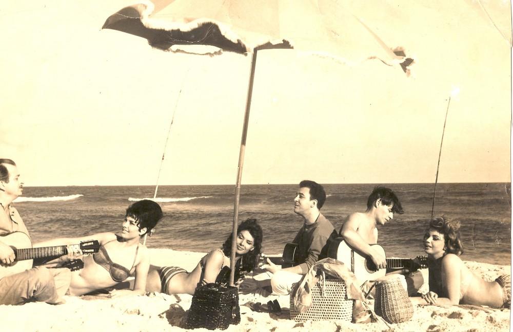 Zdjęcie w stylu sepia. Widoczna jest grupka znajomych, trzech mezczyzn i trzech kobiet lezacych pod parasolem na plazy. Trzej mezczyzni zabawiaja damy grając muzykę na gitarach i śpiewając.