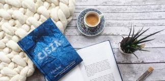 Lężąca na stole książka, obok kubek z kawą i roślina