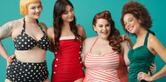 Fotografia kolorowa. Na turkusowym tle stoją cztery dziewczyny. Od lewej: Kobieta w krótkich żółtych włosach z krótką grzywką, ubrana jest w dwuczęściowy strój kąpielowy, czarny w białe grochy. Obok niej stoi kobieta z długimi ciemnymi włosami w czerwonym, jednoczęściowym sroju kąpielowy,m, który po lewej stronie ma białe guziczki. Obok stoi korpulentna kobieta w rudych włosach spiętych w kucyk, w biało czerwonym stroju w paski. Obok stoi ciemnoskóra kobieta z afro w zielonym jednoczęściowym stroju kąpielowym.