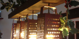Zdjecie żyrandola, który został zrobiony z tarki do sera. Na desce zwisajacej z sufity przyczepione są 4 tarki do sera, a wewnatrz nich zamocowane żarówki, które tworzą oświetlenie pokoju. Na górnej czesci przymocowanej deski leżą rośliny.