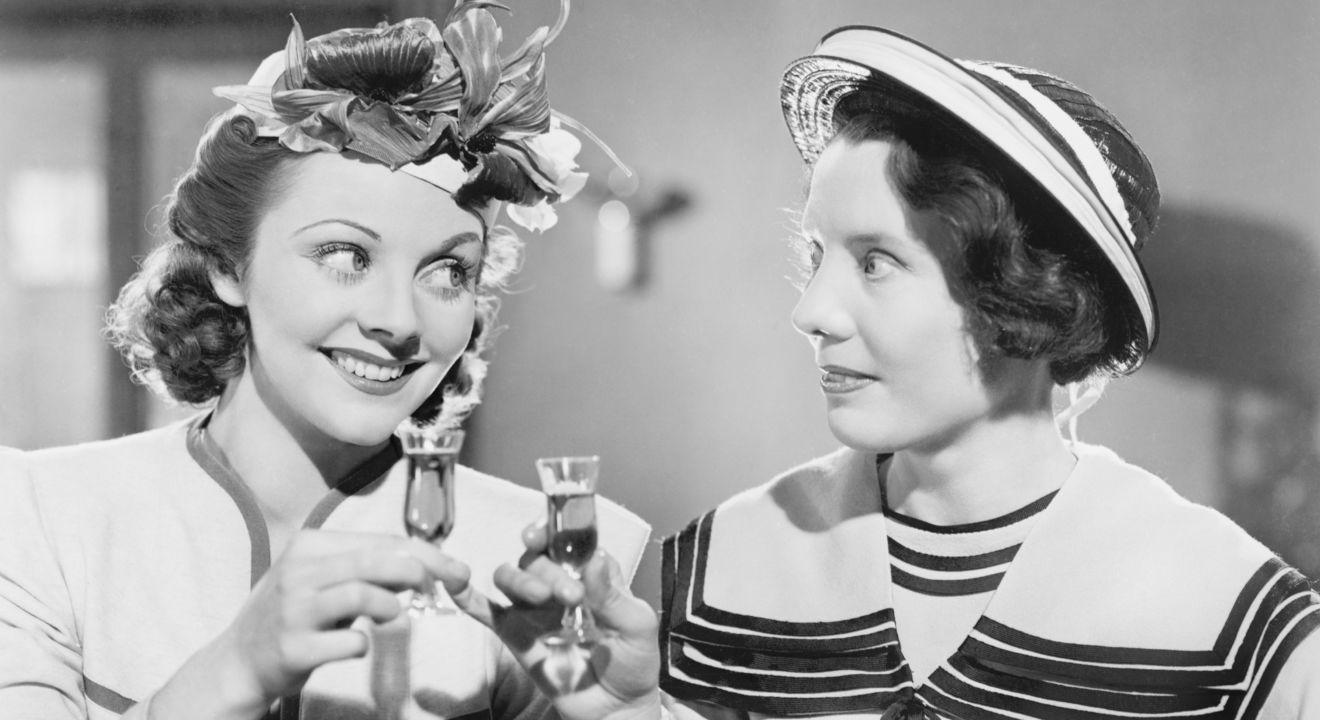 Fotografia czarno-biała, retro. Na zdjęciu widać dwie kobiety ukazane od ramion w górę. Kobieta po lewej stronie spogląda na kobietę po prawej, ma jasne, podkręcone włosy, na głowie ma toczek z kwiatów. Uśmiecha się, a w prawej ręce, dwoma palcami trzyma mały kieliszek z likierem. Kobieta po prawej stronie ma ciemne, krótsze włosy, a na głowie kapelusz z białymi paskami. Jej głowa skierowana jest w stronę pierwszej kobiety, w prawej ręce również trzyma mały kieliszek z likierem.