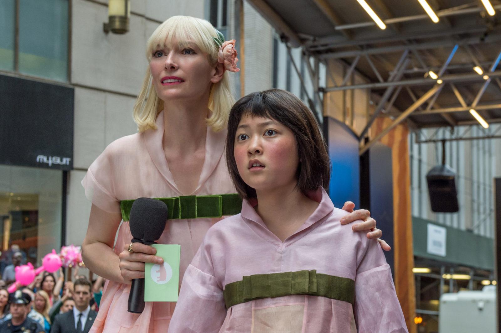 Szczupła blondynka ubrana w różowe kimono trzymająca za ramię wystraszoną dziewczynkę o azjatyckiej urodzie, która również ubrana jest w różowe kimono
