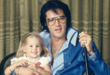 Zdjecie Elvisa Presley, ktory siedzi na krzesle ubrany w niebieski dres, w okularach, trzyma mikrofon w jednym reku, a drugą ręką trzyma siedzącą na kolanach córkę. Dziewczynka jest jeszcze w wieku przedszkolnym. W przyszlosci zostanie zona Micheala Jacksona.
