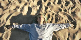 Mloda dziewczyna w turkusowych wlosach lezy z rozlozonymi rekoma w pastelowej bluzie jeansach i zamknietymi oczyma na piasku