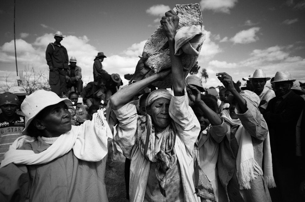 Zdjęcie ludu mieszkajacego na Madagaskarze, który kontynuuje tradycję famadihana. Wyjmują zmarłego z grobu, owijają nowymi całunami i chowają jeszcze raz. Na zdjęciu widać bliskich nieboszczyka, który trzymają go na rękach owiniętego w biały koc.