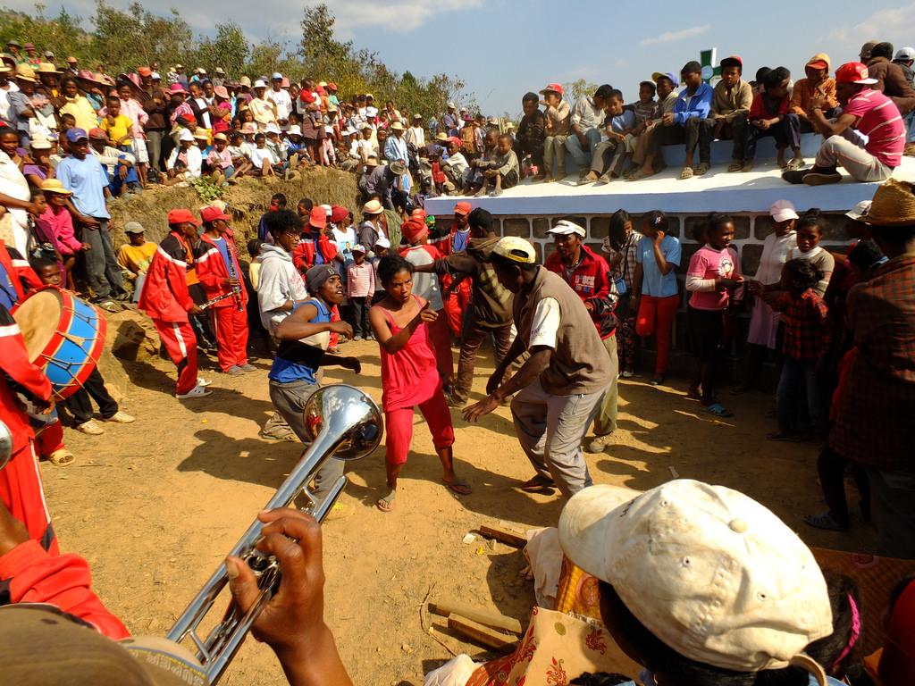 Kolorowy obrazek przedstawiający uczestników ceremonii famadihana. Widać bliskich zmarłego, którzy tańczą, grają na trąbkach, śpiewają tradycyjne pieśni ku jego czczi. Na środku wielkiego koła tańczy dwóch mężczyzn, a wokół nich zebrana jest liczna grupa ludzi.
