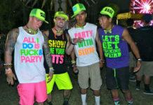 Czterech meżczyzn na festiwalu muzycznym - ubrani w koszulki z obscenicznymi napisami.