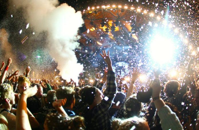 Tłum ludzi, oświetlona scena, dym