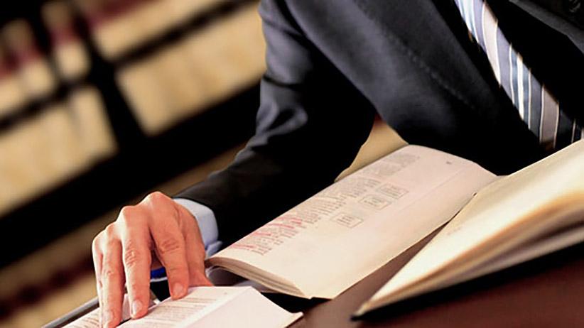 Mężczyzna w garniturze trzymający rękę na książce