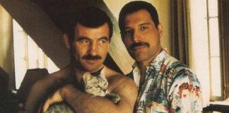 na zdjęciu są dwaj mężczyźni pozujący do zdjęcia, jeden trzyma kota na rękach