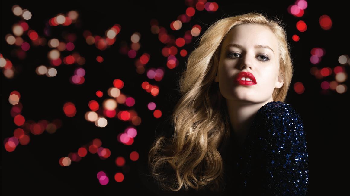 Na zdjęciu jest kobieta, blondynka, z mocno wymalowanymi na czerwono ustami, o jasnej cerze. W tle widać rózne odcienie czerwonych i różowych plamek, które prawdopodobnie są odcienami szminki.