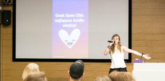 Dziewczyna w białej bluzce z mikrofonem w dłoni, na drugim planie ludzie siedzący na krzesłach
