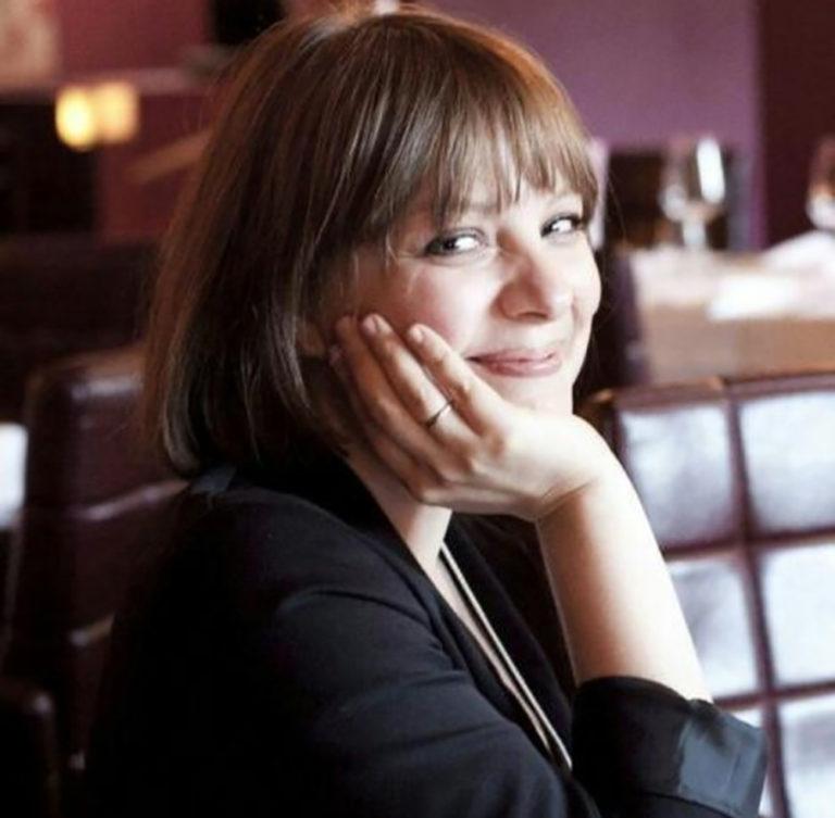Mloda kobieta siedzaca w kawiarni brunetka siedzaca profilem opierajaca glowe o dlon ubrana w czarny sweter usmiechnieta