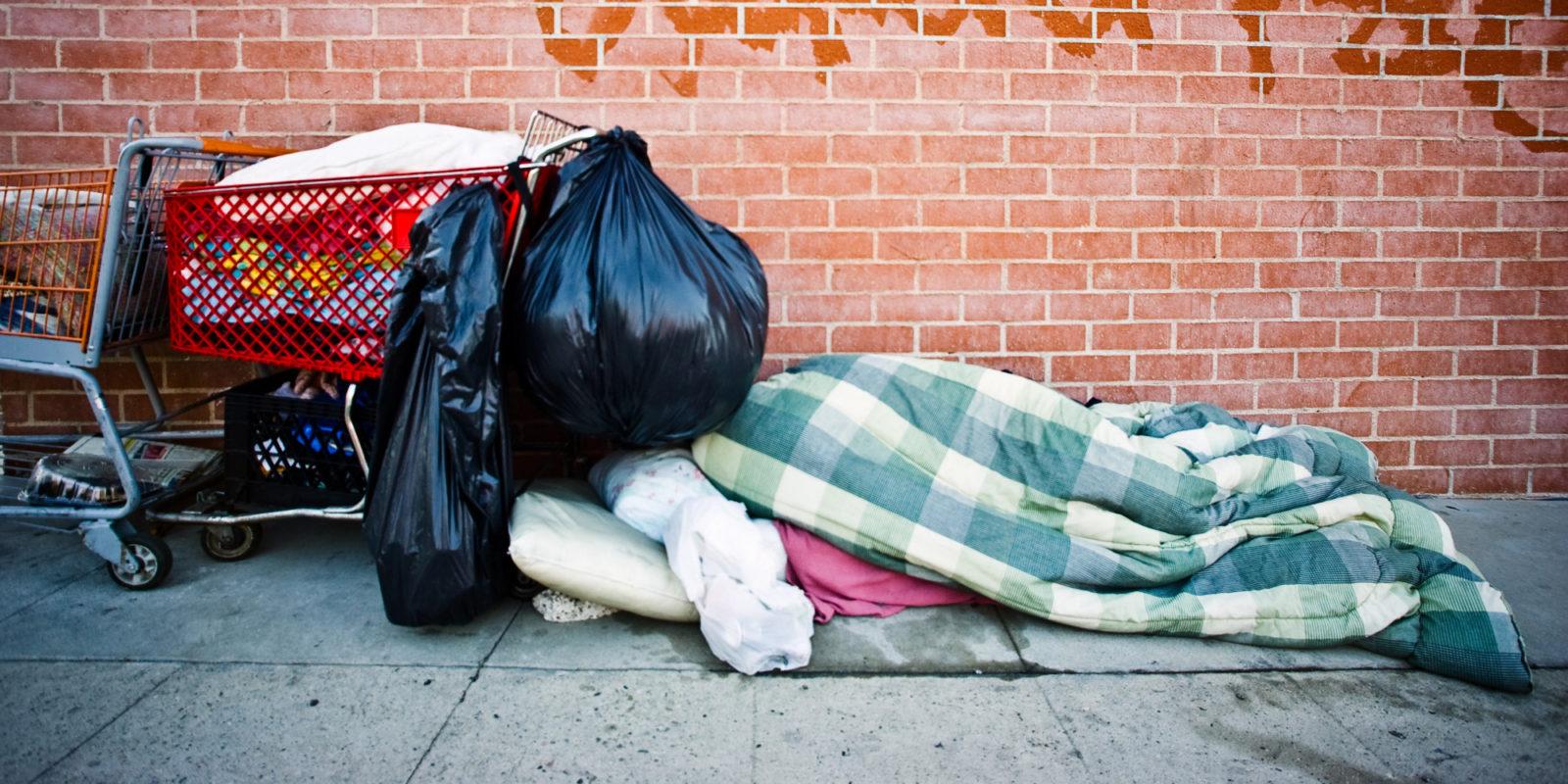 Zdjęcie jak bezdomny śpi na mieście. Widać przykrytego kocami człowiea, obok, ktorego stoi jego wózek na ktorym ma pełno toreb z swoim dobytkiem. Widać jedynie kontur osoby zakrytej kocami. Wszystko jest na tle czerwonej cegly.